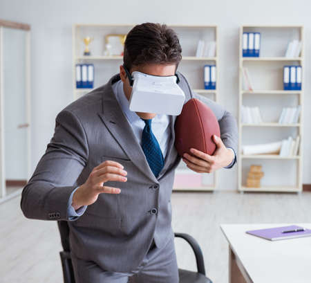 Businessman playing virtual reality football in office with VR g 写真素材 - 129990083