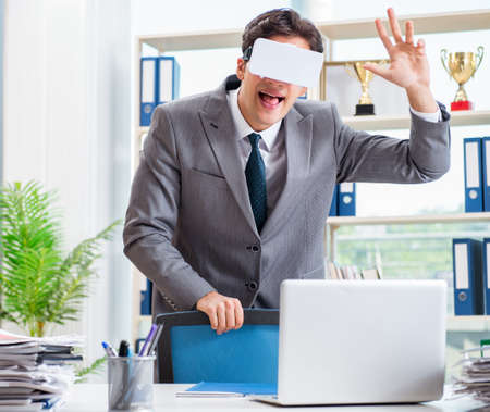 Businessman with VR virtual reality glasses in office Stok Fotoğraf