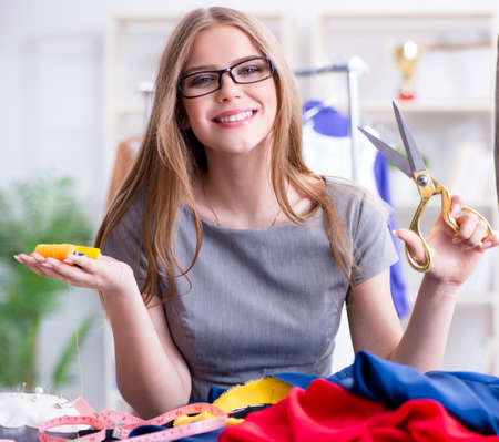 Young woman tailor working in workshop on new dress Stock Photo