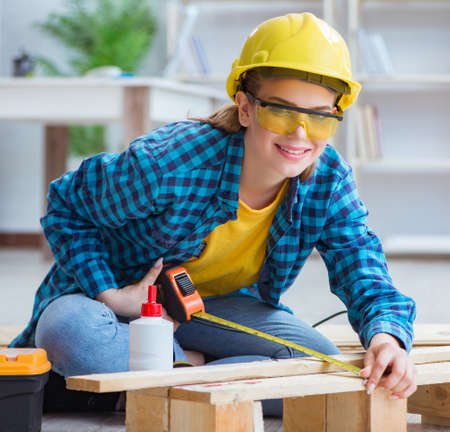 Female repairman carpenter cutting joining wooden planks doing r