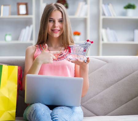 Young woman with shopping bags indoors home on sofa Standard-Bild - 129986581