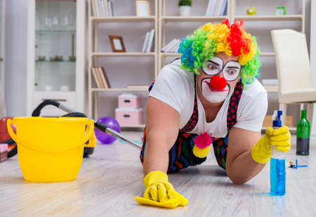 Funny clown doing cleaning at home 스톡 콘텐츠 - 129985959