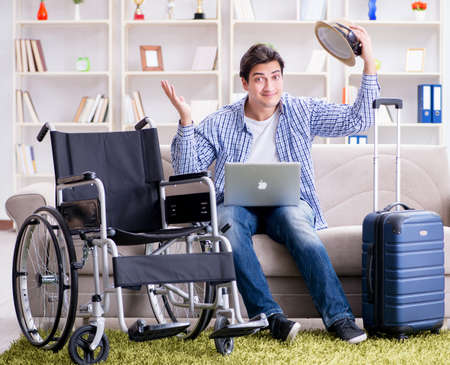 Disabled man booking travel online using laptop computer