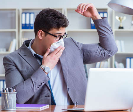 Businessman sweating excessively smelling bad in office at workp 写真素材
