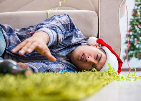 Hombre que tiene resaca después de la fiesta de Navidad