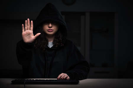 Female hacker hacking security firewall late in office 版權商用圖片