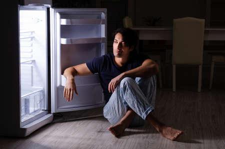 Man breaking diet at night near fridge Stock Photo