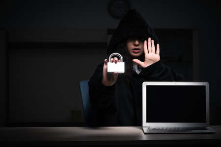 Female hacker hacking security firewall late in office Stock Photo
