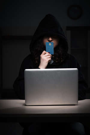 Female hacker hacking security firewall late in office Banque d'images