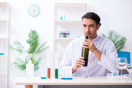 Male chemist examining wine samples at lab