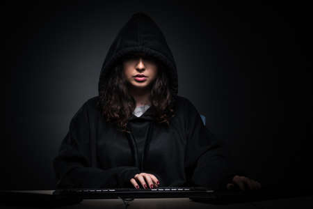 Female hacker hacking security firewall late in office