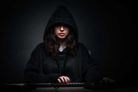 Hacker femenina hackear el firewall de seguridad tarde en la oficina Foto de archivo