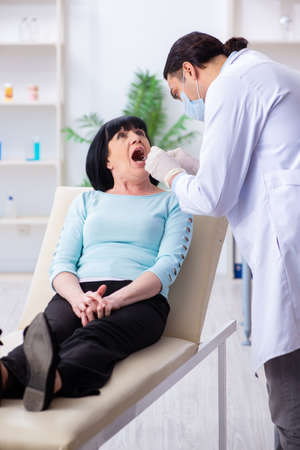 Old woman visiting young doctor dentist Stockfoto