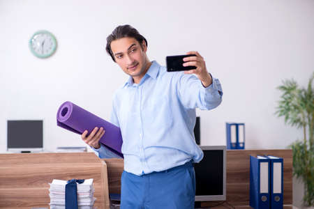 Young handsome businessman doing exercises at workplace