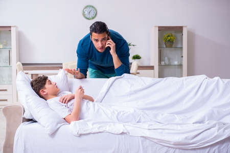 Junger Vater kümmert sich um den kranken Sohn