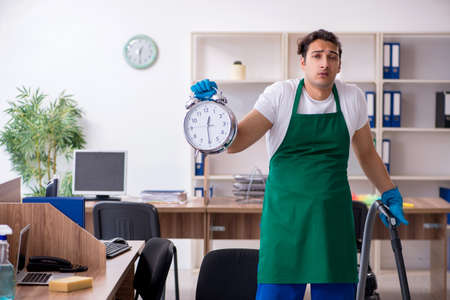 Young handsome contractor cleaning the office Stock Photo