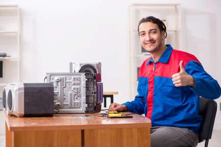 Young engineer repairing musical hi-fi system Фото со стока