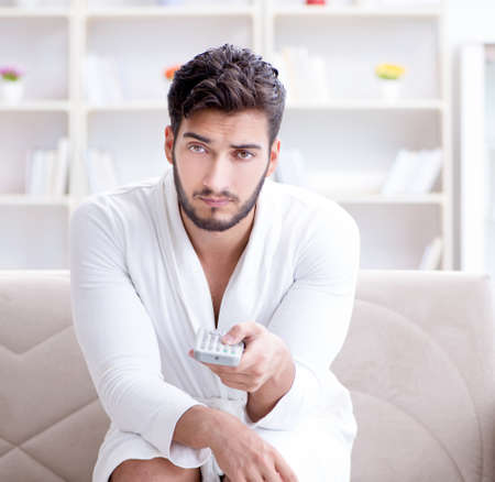 Young man in a bathrobe watching television at home on a sofa co