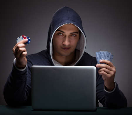 Young man wearing a hoodie sitting in front of a laptop computer 写真素材 - 130529208