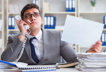 Businessman smoking at work in office holding a blank message bo Stok Fotoğraf