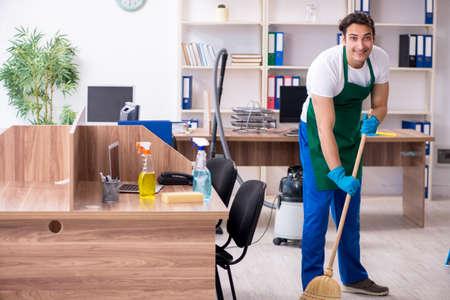 Contratista joven guapo limpiando la oficina Foto de archivo
