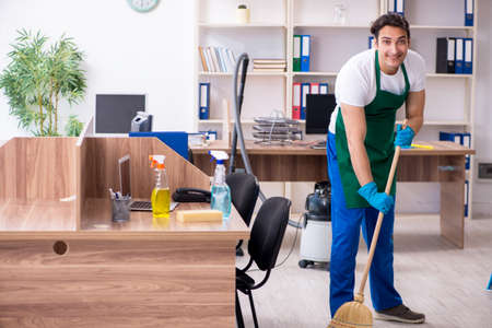 Young handsome contractor cleaning the office Reklamní fotografie