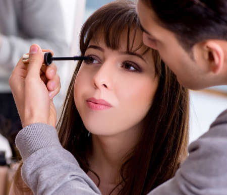 Man doing make-up for cute woman in beauty salon