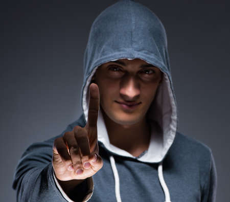 Young man wearing hoodie pressing virtual buttons Banque d'images