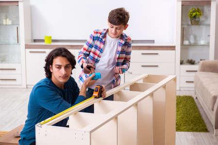 Young carpenter teaching his son