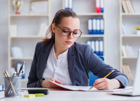 Geschäftsfrau, die im Büro am Schreibtisch arbeitet