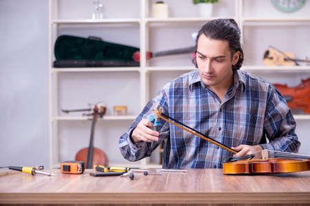 Young handsome repairman repairing violin