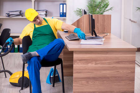 Young male contractor cleaning the office Stock Photo