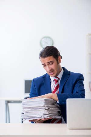 Jonge mannelijke zakenman die op kantoor zit Stockfoto