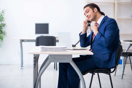 Young male businessman sitting in the office