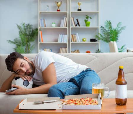 Hombre comiendo pizza con una comida para llevar en casa descansando relajante Foto de archivo