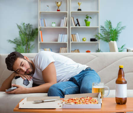 Mann, der Pizza isst, die zu Hause eine entspannende Ruhe zum Mitnehmen hat Standard-Bild