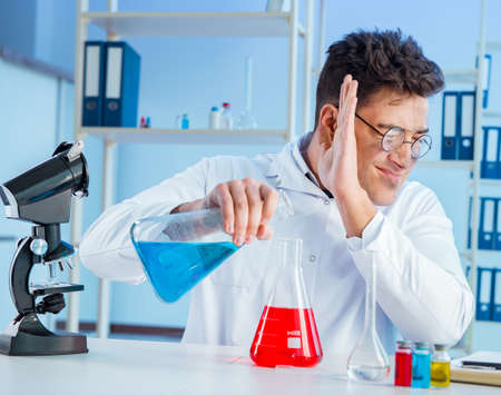 Funny mad chemist working in a laboratory Stockfoto