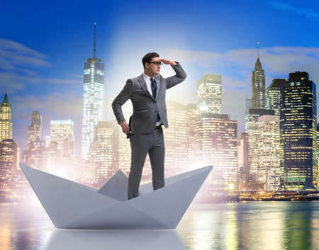 Businessman looking into future with binoculars in paper ship bo