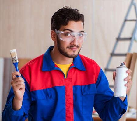 Yooung repairman carpenter working with paint painting Reklamní fotografie