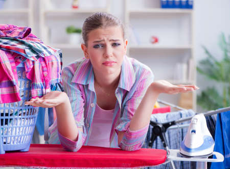 Tired depressed housewife doing laundry Stok Fotoğraf