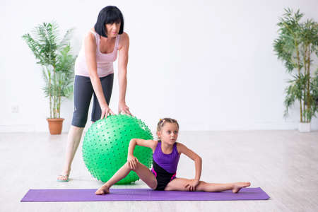 Girl and mother exercising at home Stock Photo