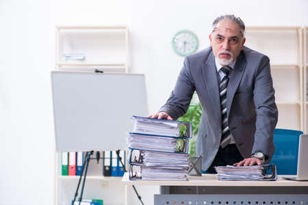 Aged male employee unhappy with excessive work Stock Photo