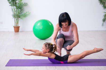 Niña y madre haciendo ejercicio en casa