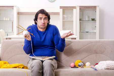 Young good looking man knitting at home Stock fotó