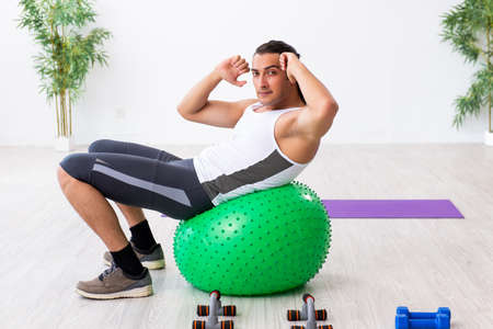 Young handsome man doing sport exercises indoors