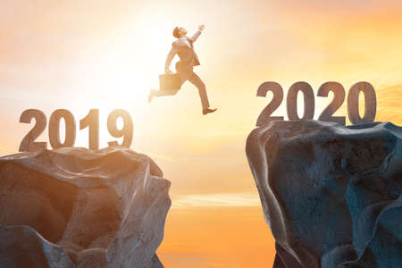 Homme d'affaires sautant de l'année 2019 à 2020
