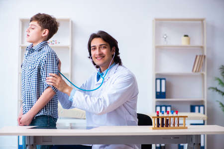 Male doctor examining boy by stethoscope
