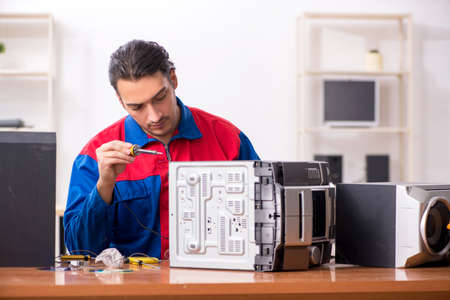 Young engineer repairing musical hi-fi system