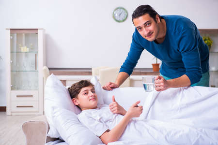Young father caring for sick son Imagens