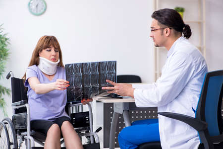 Young woman in wheel-chair visiting male doctor